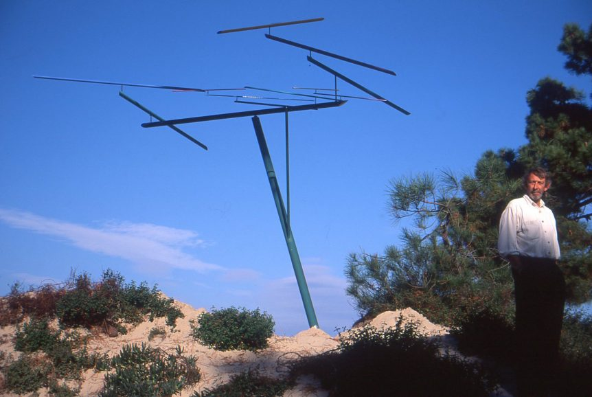 Peter Fluck stands next to his Wind-driven mobile art installation called Horizons